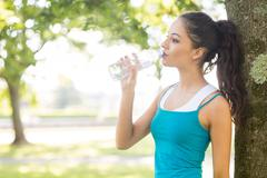 Stock Photo of Active peaceful brunette drinking from a water bottle