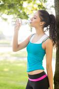 Stock Photo of Active attractive brunette drinking from a water bottle