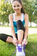 Stock Photo of Active smiling brunette tying her shoelaces