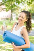 Stock Photo of Active cheerful brunette holding exercise mat