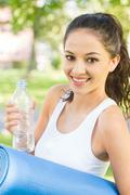 Stock Photo of Active happy brunette holding exercise mat
