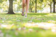 Stock Photo of Close up of female feet wearing sandals walking on grass