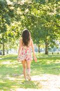 Stock Photo of Rear view of stylish brunette walking on grass