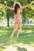 Stock Photo of Rear view of beautiful stylish brunette jumping in the air