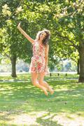Stock Photo of Stylish cheerful brunette jumping in the air