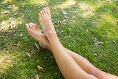 Stock Photo of Close up of crossed legs of a woman lying on the grass