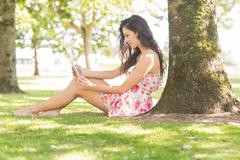 Stock Photo of Stylish attractive brunette sitting under a tree using tablet