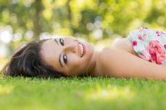 Stock Photo of Stylish smiling brunette lying on a lawn
