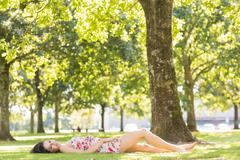 Stock Photo of Stylish attractive brunette lying on a lawn