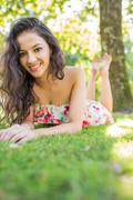 Stock Photo of Stylish cheerful brunette lying on a lawn looking at camera