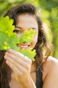 Gorgeous smiling brunette holding a leaf - stock photo