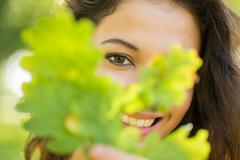 Stock Photo of Gorgeous happy brunette holding a leaf
