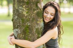 Stock Photo of Casual cheerful brunette embracing a tree with closed eyes