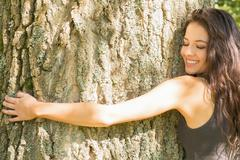Stock Photo of Casual happy brunette embracing a tree with closed eyes