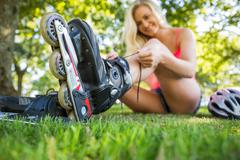Casual happy blonde putting on roller blades - stock photo