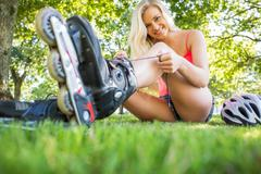 Casual happy blonde tying shoelaces of roller blades - stock photo