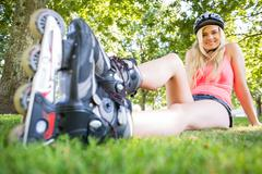 Casual attractive blonde wearing roller blades and helmet - stock photo