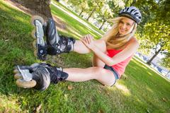 Casual cheerful blonde wearing roller blades and helmet - stock photo