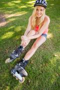 Casual content blonde wearing roller blades and helmet - stock photo