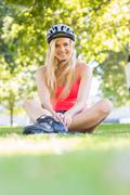 Casual smiling blonde wearing inline skates and helmet sitting - stock photo