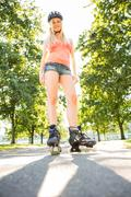 Casual smiling blonde standing in inline skates on pathway - stock photo