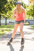 Casual smiling blonde inline skating - stock photo
