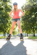 Casual smiling blonde standing hands on hips wearing inline skates - stock photo