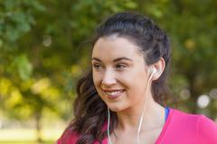 Stock Photo of Cheerful cute woman listening to music