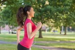 Melko urheilullinen nainen lenkillä puistossa Kuvituskuvat