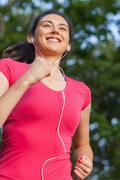 Smiling sporty woman jogging in a park Stock Photos