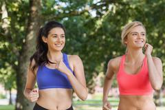 Kaksi urheilullinen naista lenkillä puistossa Kuvituskuvat
