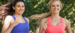 Stock Photo of Two cute sporty women running in a park