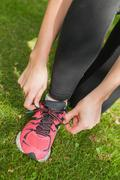 Stock Photo of Young sporty woman tying her shoelaces
