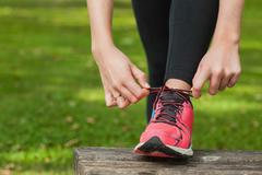 Young woman tying the shoelaces of her running shoes - stock photo