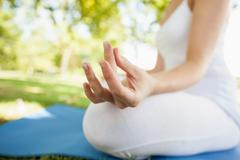 Stock Photo of Close up of peaceful woman meditating sitting on a park