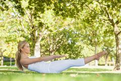 Side view of beautiful woman doing yoga in a park - stock photo