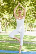 Front view of calm woman in tree yoga pose on an exercise mat - stock photo