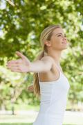 Stock Photo of Side view of cheerful attractive woman doing yoga spreading her arms