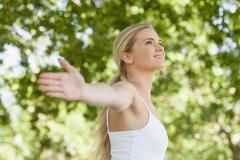 Stock Photo of Side view of pretty young woman doing yoga spreading her arms