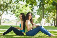 Stock Photo of Two cute brunette women sitting on a lawn smiling at camera