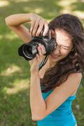 Stock Photo of High angle view of brunette young woman taking a picture