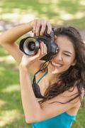 High angle view of cheerful young woman taking a picture - stock photo