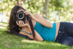 Front view of pretty brunette woman lying on a lawn taking a picture - stock photo