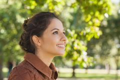 Stock Photo of Side view of cute brunette woman wearing a brown coat
