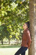 Stock Photo of Attractive woman leaning against a tree with closed eyes