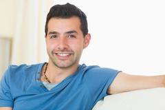 Stock Photo of Casual good looking man relaxing on couch