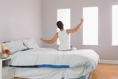 Stock Photo of Rear view of man sitting on bed stretching his arms
