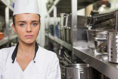 Young unsmiling chef standing arms crossed between shelves Stock Photos