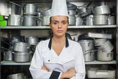 Young content chef standing arms crossed between shelves Stock Photos