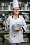 Stock Photo of Young smiling chef holding pot in front of shelf